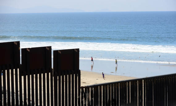 Children play on the beach at Playas de Tijuana, Mexico, across the 'border fence' which runs along the US-Mexico border some three hundred feet into the Pacific Ocean on April 4, 2013 at Border Field State Park near San Diego, California. The barrier seperating the two countries known to many as the 'border fence' or the 'border wall'  is in reality several barriers, designed to prevent illegal movement across the border, backed by supporters and criticized by opponents. Stadium beside the sea is a bull-fighting ring. AFP PHOTO/Frederic J. BROWN        (Photo credit should read FREDERIC J. BROWN/AFP/Getty Images)