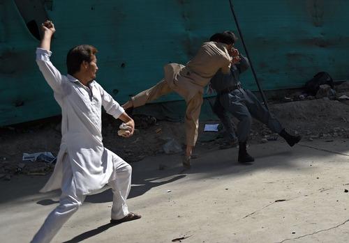 معترضان افغان در حال کتک زدن یک نیروی پلیس پس از واقعه 3 انفجار انتحاری در تظاهرات مسالمت آمیز جنبش روشنایی در کابل