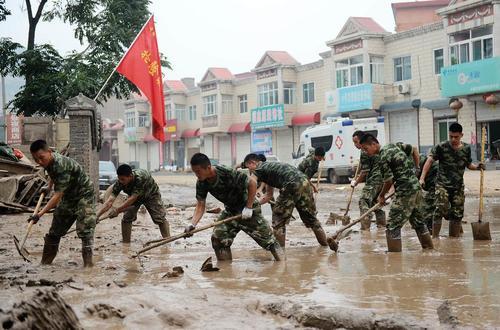 سربازان چینی در حال تمیز کردن خیابان از گل و لای و استحکام بندی در برابر سیل