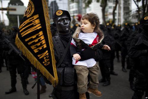 سرباز ارتش پرو پیش از انجام رژه روز استقلال این کشور در شهر لیما در حال گرفتن یک عکس یادگاری با یک کودک است