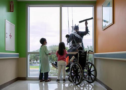 پاک کردن شیشه های بیمارستان کودکان در پالم بیچ فلوریدا آمریکا در لباس بتمن