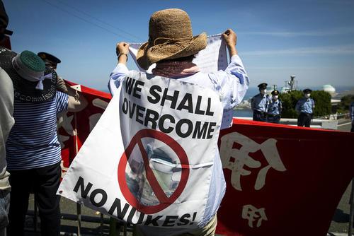 تجمع مخالفان انرژی هسته ای در مقابل نیروگاه هسته ای ایکاتا ژاپن در اعتراض به از سرگیری فعالیت این نیروگاه