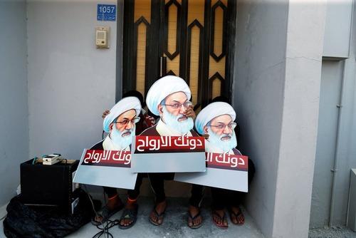 پلاکاردهای تصویر شیخ عیسی قاسم روحانی شیعه مخالف حکومت بحرین در دست حامیانش – بحرین
