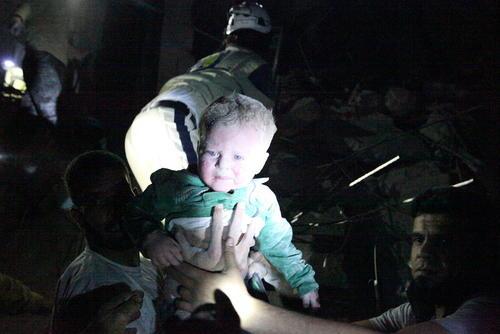 بیرون کشیدن یک نوزاد از زیر آوار بمباران هوایی در شهر حلب سوریه
