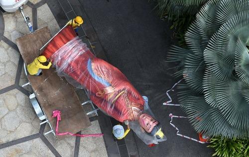 جابجایی مجسمه یک قهرمان اسطوره ای برای بردن به داخل باغی در سنگاپور برای یک جشنواره پاییزی