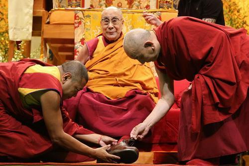 جلسه درس دالایی لاما رهبر در تبعید بوداییان تبت برای راهبان بودایی در شهر استراسبورگ فرانسه . راهبان در حال درآوردن کفش دالایی لاما هستند