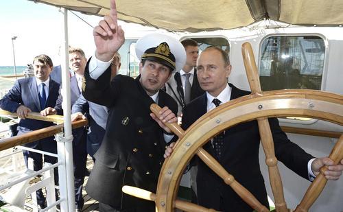 رییس جمهور روسیه و سکانداری کشتی در بازدید او از پایگاه نیروی دریایی روسیه در شهر بندری سوچی