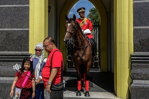 کس یادگاری توریست ها با گارد مقابل کاخ ملی مالزی – کوالالامپور