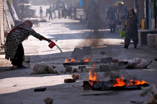 زنان کشمیری در حال آتش زدن اجسام برای در امان ماندن از اثرات گاز اشک آور پلیس هند