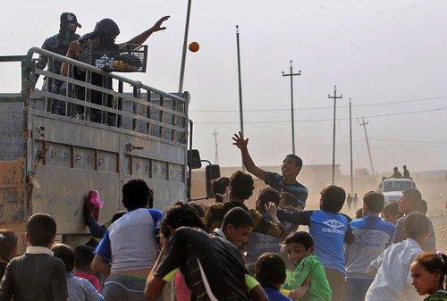 نیروهای عراقی در حال توزیع میوه بین کودکان در روستایی در نزدیکی موصل