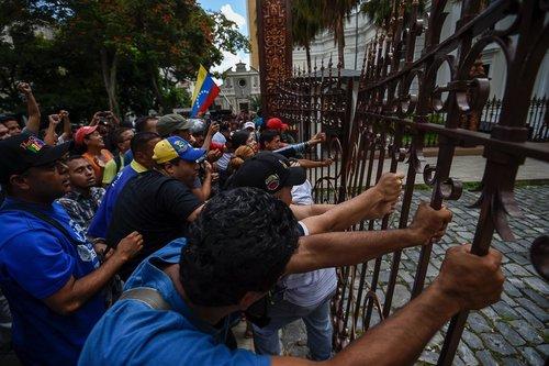 هواداران نیکولاس مادورو رییس جمهور ونزوئلا دروازه ورودی ساختمان پارلمان را می شکنند تا اعتراض خود را به جلسه اضطراری پارلمان این کشور با درخواست اپوزیسیون این کشوردرباره آینده مادورو ابراز کنند