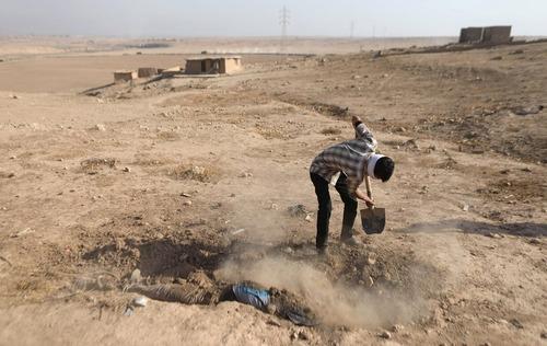 یک مرد عراقی در حال دفن کردن جسد یک تروریست داعشی در جنوب شهر موصل