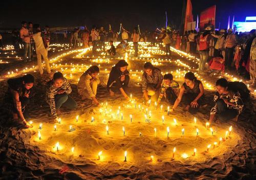 روشن کردن شمع در جشنواره آیینی هندوها در حاشیه رود گنگ در الله آباد هند
